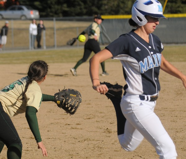 The University of Maine's EmJ Fogel (right) runs to first base, beating the throw to Husson University's Nicole Sargent during the third inning in Bangor Tuesday afternoon. Maine won 9-0.