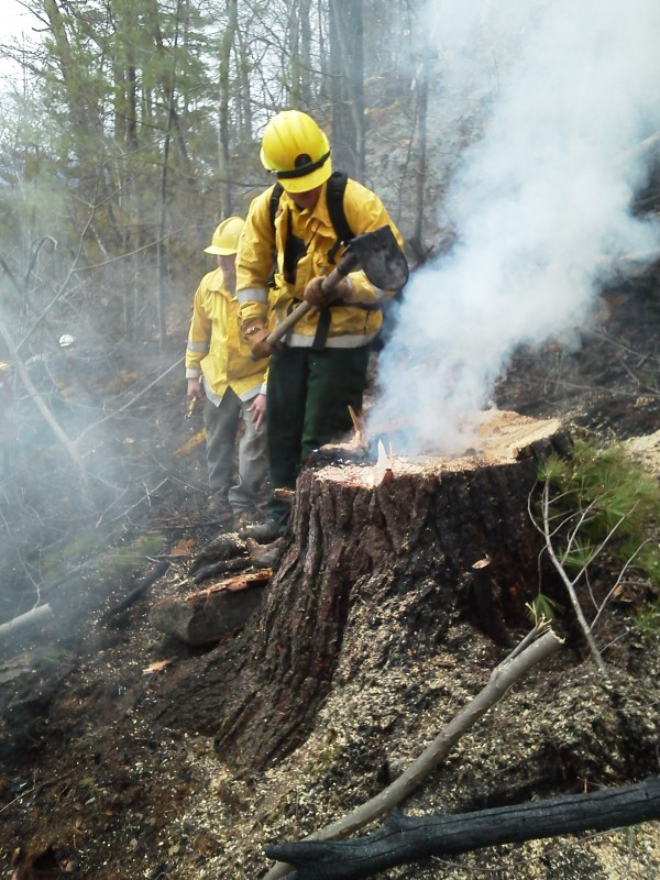 Maine Forest Service Forest Ranger Art Lavoie works Thursday at a fire in a mountainous area of Gilead. Four forest rangers were at the scene along with about 24 local firefighters. A Maine Forest Service helicopter was making repeated drops at the fire scene, getting water from the nearby Androscoggin River.