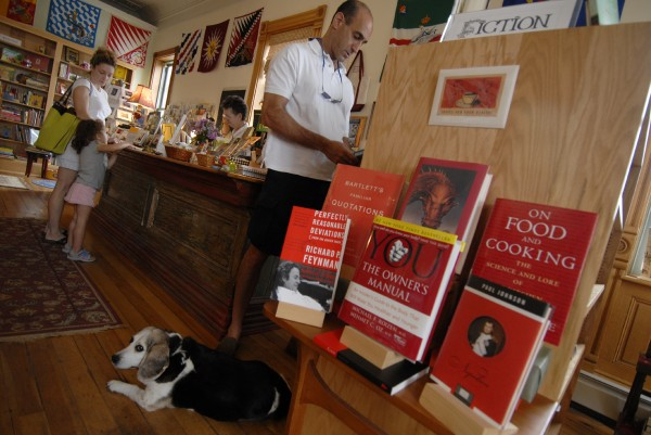 At Left Bank Books in Searsport in August 2006, Michael Medelowitz of Tampa, Fla., looks for fiction as his wife, Lisa, and their daughter Ella, 3, get a little help from store co-owner Marsha Kaplan. On the floor is Patty, Kaplan's 12-year-old beagle.
