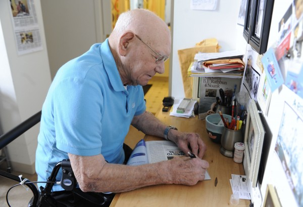 James Arruda Henry autographs a recent article in a magazine about him at his apartment in Mystic, Conn., Wednesday, March 28, 2012. The 98-year-old retired lobsterman published his autobiographical essays after learning to read and write in his 90s.