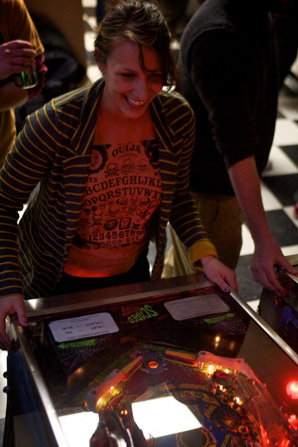 Kristine Pennell of the Ouija Conspiracy team plays the Scared Stiff machine at the weekly Coast City Comics pinball tournament.