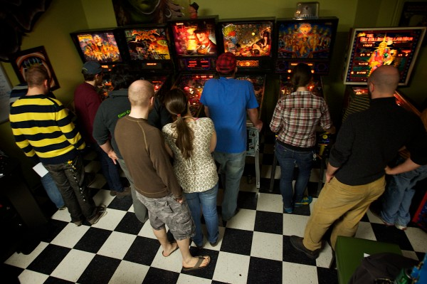 Ten of 14 players at the weekly Coast City Comics pinball tournament gather round the tables at the back of the store.