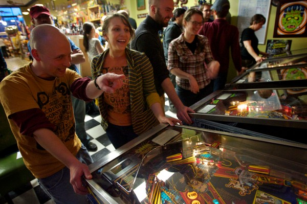 Steve Morris and Kristine Pennell of the Ouija Conspiracy team each operate a flipper at the weekly pinball tournament at Coast City Comics on Congress Street in Portland.