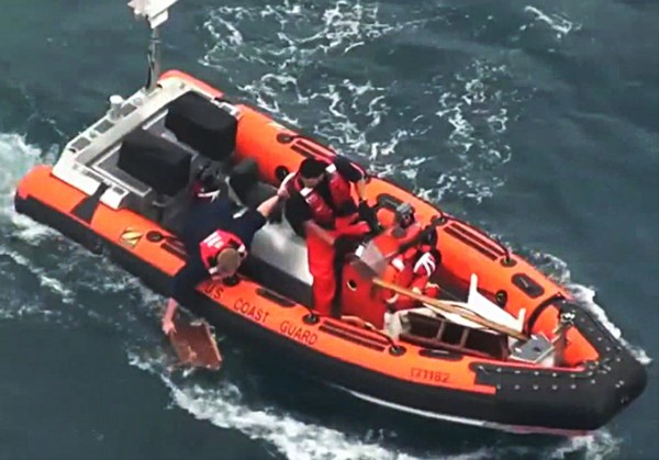In this image taken from U.S. Coast Guard video, a rescuer retrieves a piece of debris from the ocean off the Baja California, Mexico coast near Ensenada Sunday, April 29, 2012. The 37-foot racing sailboat Aegean, carrying a crew of four, was reported missing Saturday, the U.S. Coast Guard said. The yacht appeared to have collided at night with a much larger vessel, leaving three crew members dead and one missing.