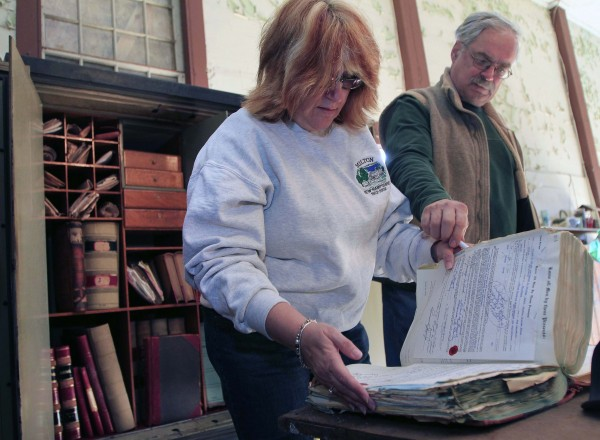 Town Clerk and Tax Collector Anne Clark looks through old ledgers from the town safe with Town Administrator Tony Mincu in the old town hall, Saturday, April 14, 2012 in Milton, N.H. The safe had been locked for decades after the combination had been lost. The town had to hire a safecracker to open the safe.