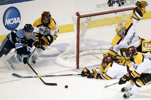 Maine's Matt Mangene (left) tries to get to a loose puck in front of Minnesota-Duluth goaltender  Kenny Reiter as Reiter gets help from teammates Brady Lamb (2) Drew Olsen and Derik Johnson (4) during their Northeast Regional contest on March 24 in Worcester, Mass. Mangene has left the Bears a year early to pursue a pro hockey career.