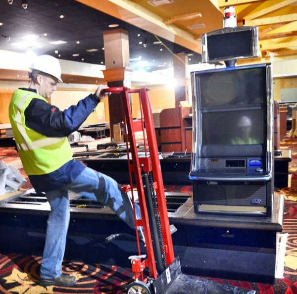 Oxford Casino employee Erik Franzen removes a hand truck used to move the first slot machine, background, into place on March 29, 2012, at the new Oxford Casino.
