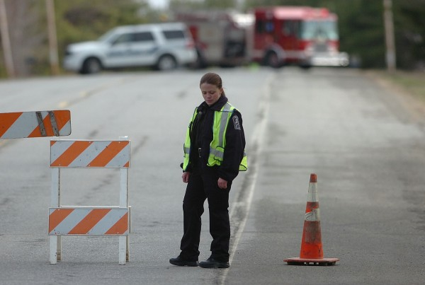 Old Town patrol officer Christine McAvoy helps secure the perimeter in front of a police and fire department blockade to the fatal vehicle accident in the Route 2 area of Old Town early Tuesday morning, April 10, 2012.