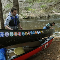 A competitor drags his canoe over the top of another racer's boat at a portage during the Passagassawakeag Stream Canoe Race on Saturday, April 7, 2012. Low water had the racers doubling back and paddling upstream for the last half of the race.