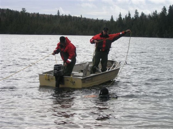 Cpl. Mike Joy (left) and Wardens Bruce Loring and Mike Pierre (in the water) during Tuesday's Blake Lake search.