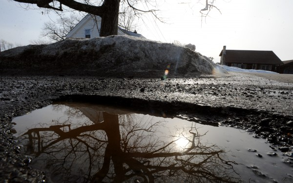 A water-filled pothole reflects the landscape on the Snows Corner Road in Orrington in March 2009.