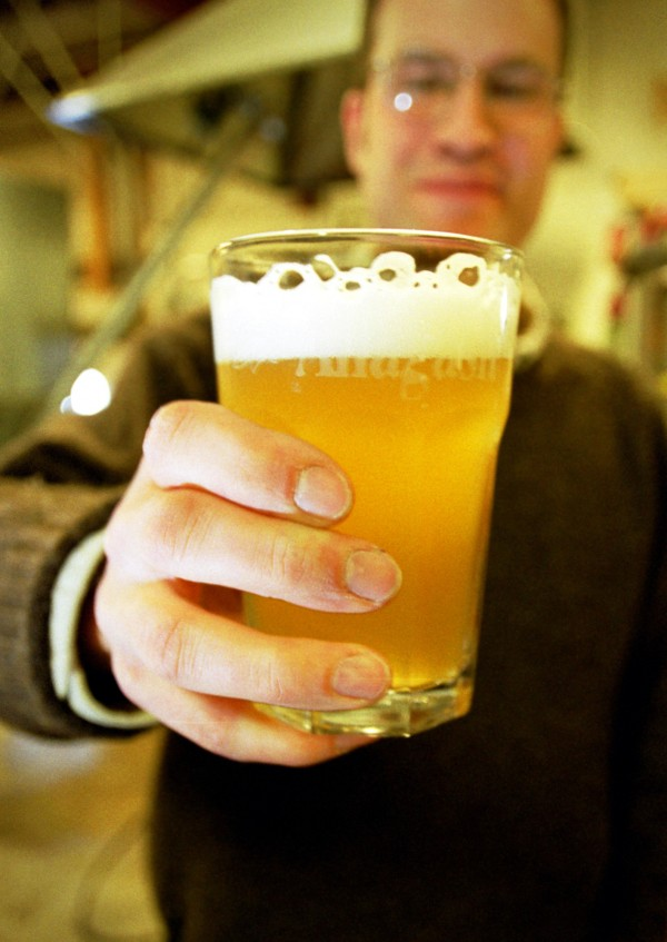Rob Tod holds a glass of Belgian-style wheat beer produced at his Allagash Brewing Co. in Portland.