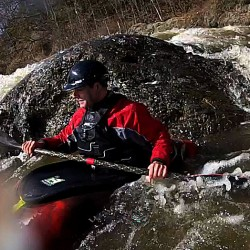 "Nicholas Wood waits in the eddy formed behind a boulder at the rapid paddlers refer to as ""the corner"" below the Valley Avenue Bridge drop on the Kenduskeag Stream.  The stream iced out unusually early making this March 13th run possible."