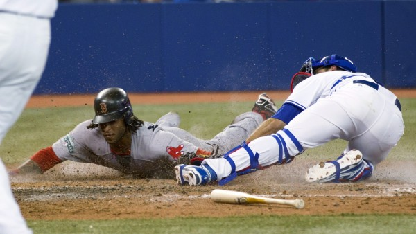 Boston Red Sox pinch runner Darnell McDonald scores past Toronto Blue Jays catcher J.P. Arencibia during the ninth inning  in Toronto on Monday night, April 9, 2012.