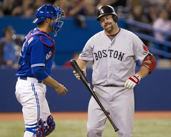 Boston's Kevin Youkilis reacts in front of Toronto Blue Jays catcher J.P. Arencibia after striking out in the ninth inning of  Wednesday's loss in Toronto. The Red Sox play their home opener Friday against Tampa Bay and will try to turnaround a 1-5 start.
