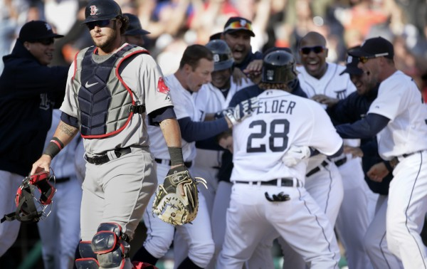 Boston Red Sox catcher Jarrod Saltalamacchia, left, walks off the field as Detroit Tigers celebrate a 13-12 win in 11 innings, after a baseball game Sunday, April 8, 2012, in Detroit.