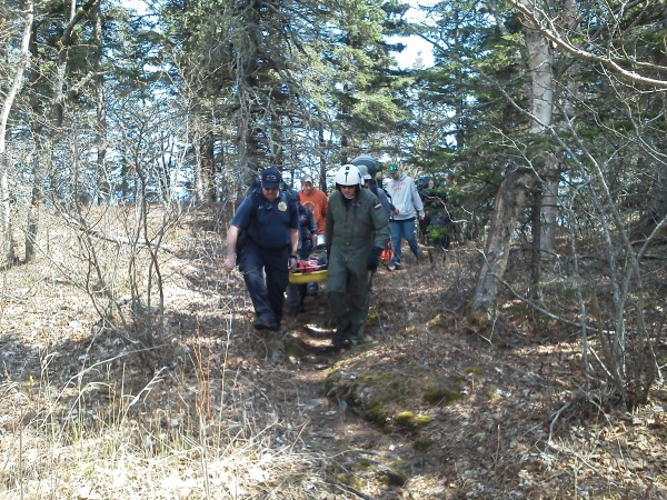Rescuers carry an injured hiker to a waiting Maine Forest Service helicopter on Sunday in Cutler.