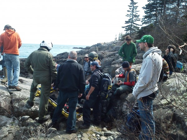 Rescuers tend to an injured hiker in Cutler on Sunday afternoon. The College of the Atlantic student twisted her leg as she tumbled a few feet from the Bold Coast Trail onto a rock face on Sunday.