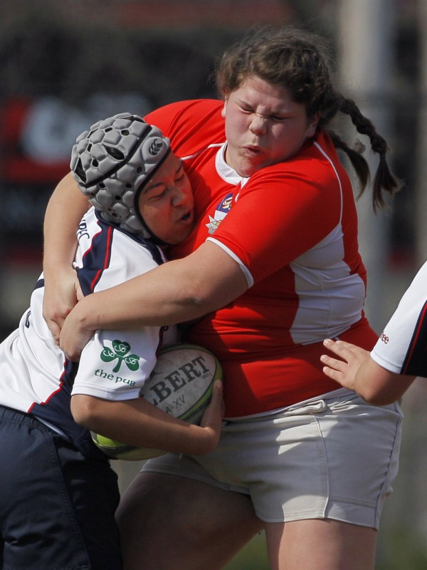 Portland's Abby Vogel (right) wraps up a Boston player during a match Saturday, April 14, in Portland. &quotGirls who crave a contact sport, something physical, are drawn to rugby,&quot team president Brittney Braasch said.