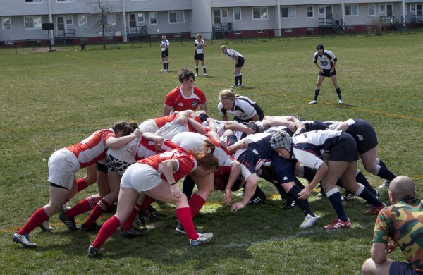 The Portland Women's Rugby Club, in orange shirts, and Boston form a scrum as they compete for the ball in a match Saturday, April 14, in Portland.