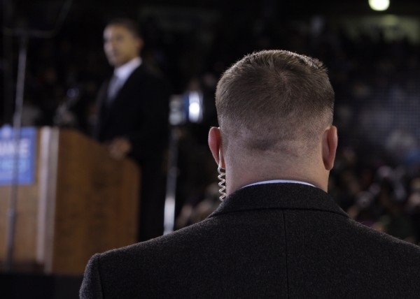 A Secret Service agent stands near then presidential candidate Barack Obama, background, at a rally in Norfolk, Va. Moving swiftly, the Secret Service forced out three agents Wednesday, April 18, 2012 in a prostitution scandal that has embarrassed President Obama.