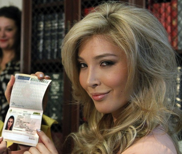 In this April 3, 2012, photo, Jenna Talackova, who advanced to the finals of the Miss Canada competition, part of the Miss Universe contest, shows her passport that lists her gender as female, during a news conference in Los Angeles. Talackova says she was forced out of the competition because Pageant officials alleged she was not &quota naturally-born female.&quot