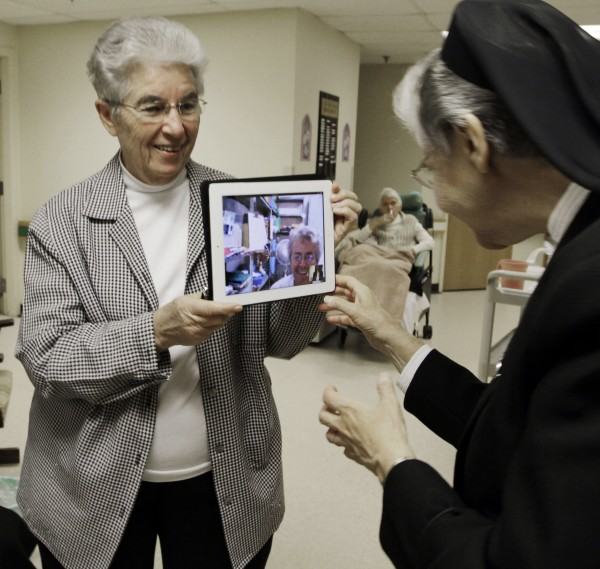 Sister Priscille Roy (left) holds an iPad displaying her colleague, Sister Pauline Demers, who is in Brazil, to show Sister Elaine Lachance (right) at St. Joseph Convent in Biddeford on Tuesday, April, 10, 2012. Good Shepherd Sisters of Quebec has just six convents in Maine and Massachusetts with fewer than 60 sisters. Sister Lachance is using the Internet, social media and a blog to attract women who feel the calling to serve God.
