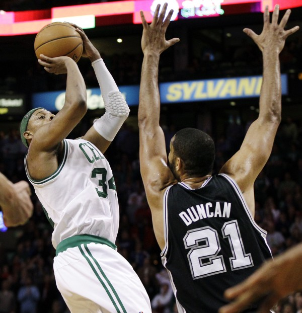 San Antonio Spurs center Tim Duncan (21) defends against a shot attempt by Boston Celtics forward Paul Pierce (34) in the last seconds of an NBA basketball game in Boston, Wednesday, April 4, 2012. The Spurs won 87-86.