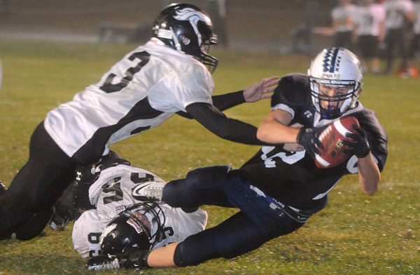 Billy Eurich (right) of Stearns High of Millinocket escapes the tackle attempts of Calais-Woodland's Ryan Cavanaugh (top left) and Jacob Sterner and dives into the end zone for a touchdown in a September 2010 game in Millinocket.