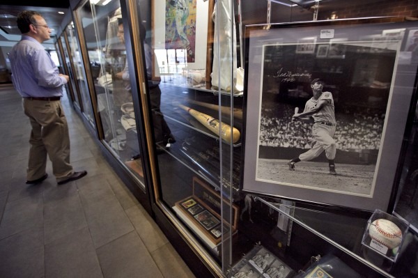 Baseball fan Sumner Friedstein (left), of West Newbury, Mass., views items once owned by Boston Red Sox's Ted Williams near a photograph of Williams from the 1942 season, right, in a display case at Fenway Park during an auction preview, Wednesday, April 25, 2012, in Boston. Fans are able to see hundreds of items during the preview which is to last through Friday. The auction is to be held Saturday, April 28.