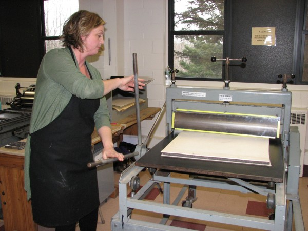 University of Maine at Machias student Hosanna Jensen uses an etching press to make a print in the UMM Book Arts Studio. The institution was recently awarded a $30,000 grant to add a high-speed bindery to its printing shop.