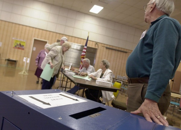 Standing by the ballot box, ward clerk Charlie Rich watches as voters at the Abraham Lincoln School in Bangor prepare to cast their votes on the proposed racino in the city and state bond issues in June 2003.