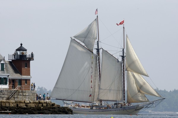 The Heritage passes the Rockland Breakwater Lighthouse during the Maine Windjammer Parade in Rockland, Maine. Maine's peacefulness has drawn visitors to the state for many years.