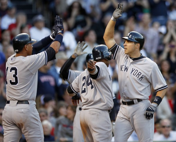 New York Yankees' Mark Teixeira, right, celebrates his three-run home run that drove in Alex Rodriguez (13) and Robinson Cano (24) in the seventh inning against the Boston Red Sox in Boston, Saturday, April 21, 2012.