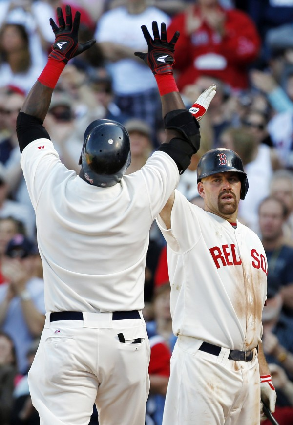 Boston Red Sox's David Ortiz (left) celebrates his solo home run with Kevin Youkilis in the second inning of a baseball game against the New York Yankees in Boston on Friday, April 20, 2012.