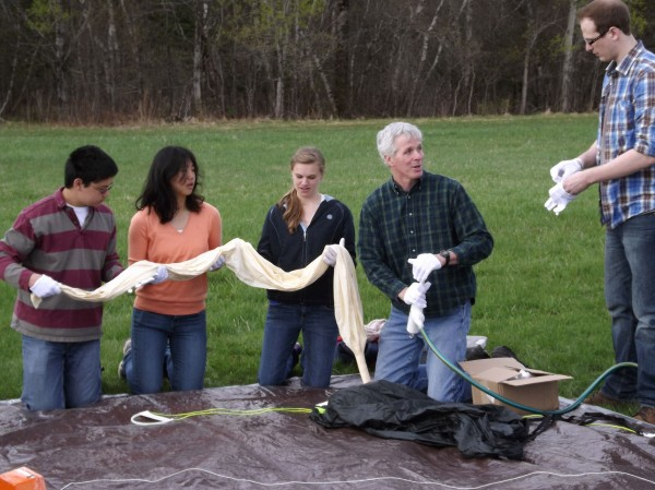 University of Maine associate professor of electrical and computer engineering Rick Eason (second from right) talks with a UMaine student as three Bangor High School students hold a deflated balloon in preparing for a high-altitude balloon launch at Pittsfield Municipal Airport on Wednesday, April 25, 2012.