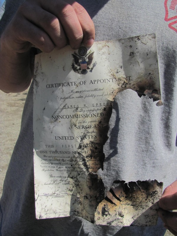 Adam Sproul, the son of James Michael Sproul, who died Wednesday morning in a fire in Boothbay, holds a half-burned certificate from when his father was appointed a master sergeant in the U.S. Air Force. Sproul said the certificate is one of the few recognizable items he found in the rubble.