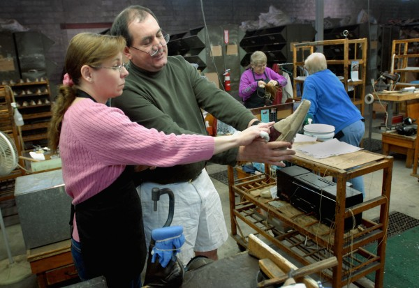 Adam Sutton, president of Highland Shoe in Brewer, looks over a product with employee Barbara White on Thursday.