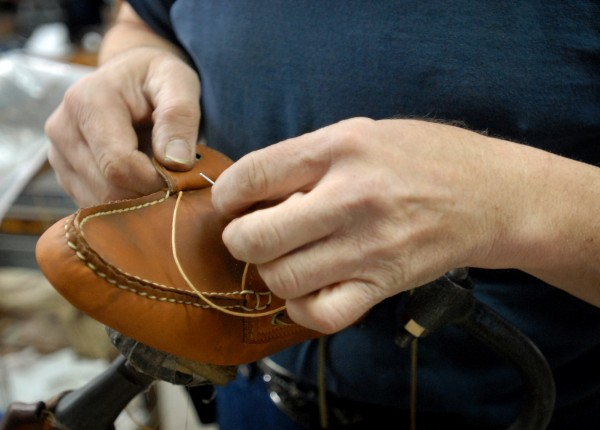 Steven Cyr hand sews a Sperry boat shoe at Highland Shoe on Thursday.