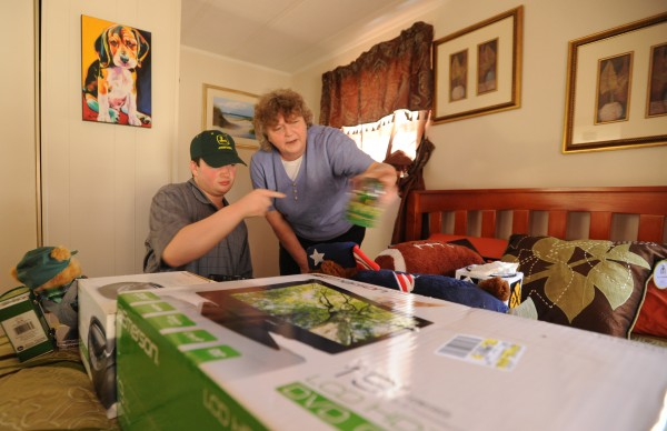 Cindy Burke (right) and her son Casey unpack personal belongings in Casey's new bedroom in Bangor on Tuesday, April 17, 2012. Casey has been moved into a group home with trained staff members to assist him with his autism.