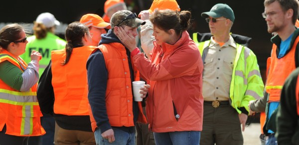 Volunteer searcher Cote Rossingnol is comforted by a woman on Wednesday, April 25, 2012 after searchers were briefed by game wardens and informed that the body of Dean Levasseur had been found in a dense area of woods not far from the point where he was last seen by band mate Josh Hunnefeld on Saturday, April 21, 2012 during the Chickenfest party in Howland.