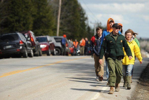A game warden leads a group of seachers down Lagrange Road on Tuesday, April 24, 2012 to search a wooded area for Dean Levasseur who has been missing since Saturday, April 21, 2012.