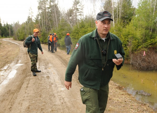 Maine Game Warden Dave Georgia leads a group of searchers out of the woods in Howland on Tuesday, April 24, 2012 after a grid search to locate Dean Levasseur who has been missing since Saturday.