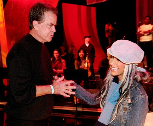 In this Jan. 11, 2003 file photo, Dick Clark greets singer Christina Aguilera during rehearsals for the American Music Awards in Los Angeles.