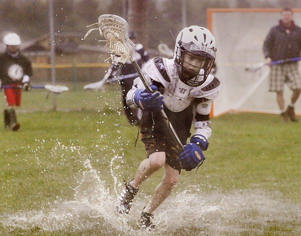 Christopher Johnson of Hampden takes a splash on the rain-soaked field to snatch up the ball during Eastern Maine Youth Lacrosse practice on Union Street in Bangor, Monday, April 23, 2012.