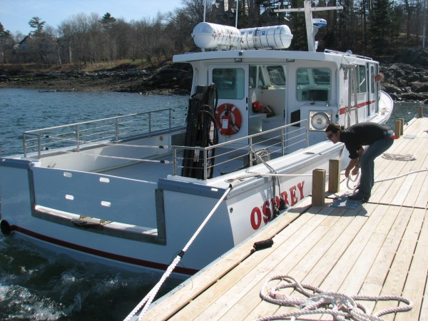 College of the Atlantic student Alex Borowicz ties up the Osprey to the COA dock on Tuesday, April 17, 2012, as Captain Toby Stephenson looks on. The boat, which replaces the smaller Indigo, was built last winter and launched last week in preparation of the college's 2012 marine program season.