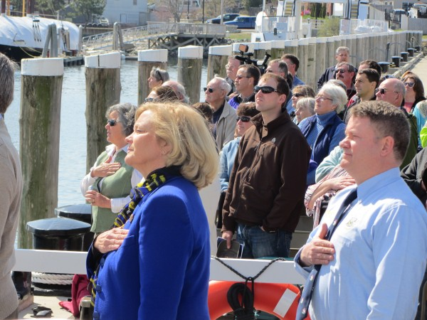 U.S. Rep. Chellie Pingree (left foreground), D-Maine, and Deputy Maine Department of Transportation Commissioner Bruce Van Note stand at attention during the playing of the national anthem during the christening ceremonies for the new state ferry.