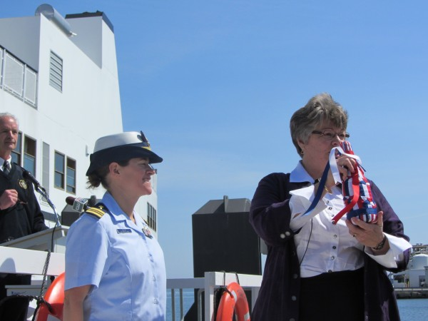 Than Hopkins, the daughter of the new ferry's namesake, holds the ceremonial champagne bottle that she later used to christen the Captain E. Frank Thompson. Chaplain Cynthia Kane, a lieutenant commander for the U.S. Navy Chaplain Corps, stands to Hopkins' left after leading a prayer.