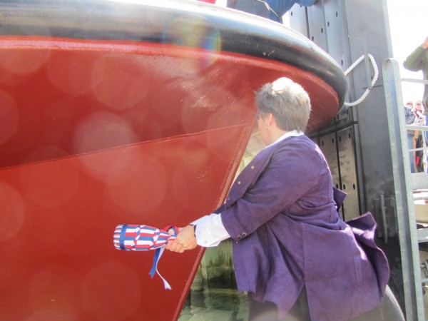 Than Hopkins takes a swipe at the newest Maine ferry during christening ceremonies Friday in Rockland. Hopkins is the daughter of the late Capt. E. Frank Thompson, for whom the vessel is named.