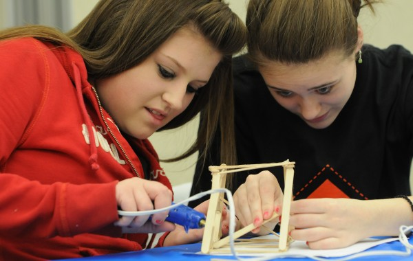 Maine Central Institute students Courtney Sprague (left) and Olivia Hamm work together to build a wooden bridge from popcicle sticks during the 10th annual Totally Trades! conference at the United Technologies Center in Bangor on Friday, April 6, 2012.